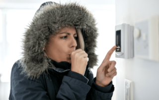 Cold woman using the thermostat