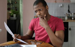 man contemplating electricity bill