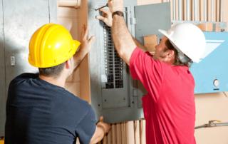 electricians repairing circuit breaker panel