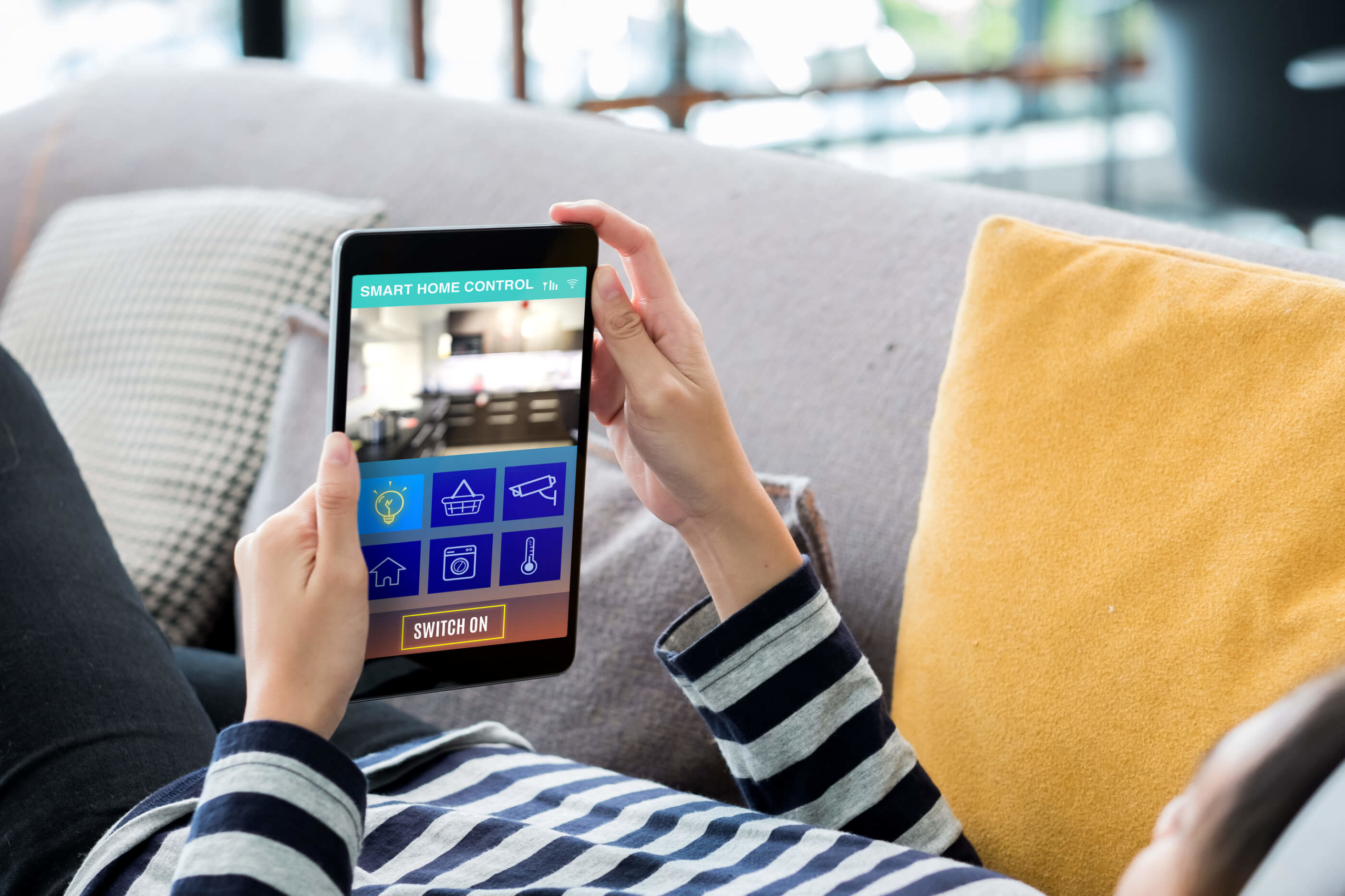 home-automation-woman-on-couch-control-device