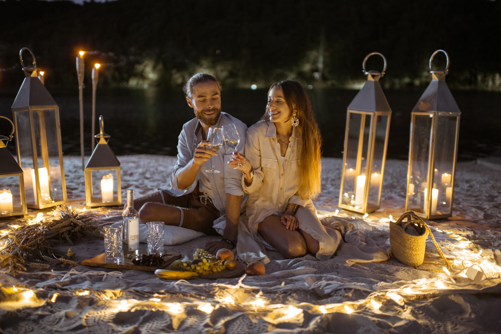 Couple-Having-A-Romantic-Dinner-on-the-beach-with-lighting