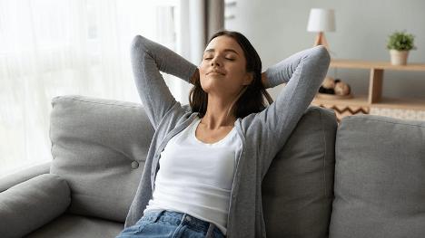 Woman relaxing on grey sofa